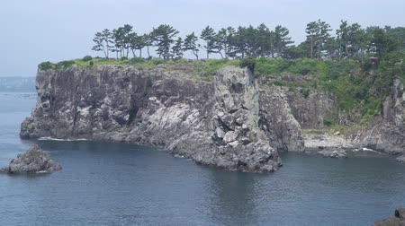 monolith : Oedolgae rock and hill of storm, view from Olle trail course No.7 in Jeju island, Korea. The rock and hill is famous for a filming place of the drama Daejanggeum.