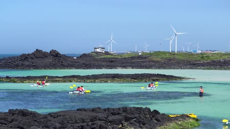 přímořská krajina : Jeju, Korea - May 22, 2017: People kayaking in Woljeongri coast. Worljeongri coast is famous for clean white sand and emerald-blue water. And also many people enjoy kayaking at the coast. Dostupné videozáznamy
