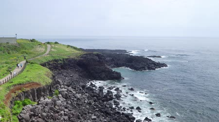вулканический : Jeju, Korea - May 23, 2017: Seopjikoji is a cape at the end of the eastern shore of Jeju Island. The place is famous for the filming site of cinemas and dramas, including All In and Ginko bed. Стоковые видеозаписи