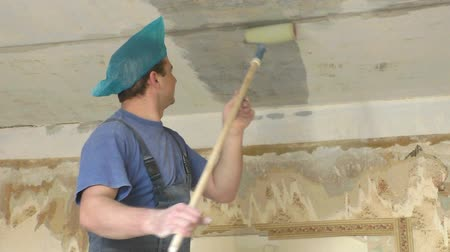 Worker with roller in hands covers the ceiling with primer Stock Footage