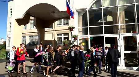 RUSSIA, MOSCOW, 1 SEPTEMBER 2016 - Happy children with bouquets of flowers go to secondary school at the Day of Knowledge Stock Footage