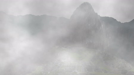 терраса : The ancient Incan city of Machu Picchu shrouded in and appearing from fog.