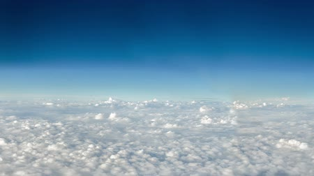 beautiful view : White fluffy clouds moving against a deep blue sky as seen from above. Stock Footage