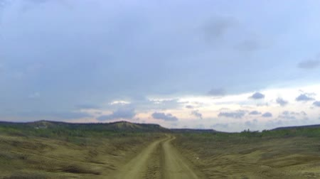 Колумбия : Driving on a dirt road in a desert at dusk with with goats crossing the road in La Gaujira, Colombia