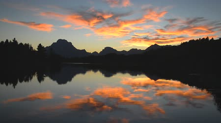 grand tetons : Fast motion view of bright colorful sunset reflected in the Snake River in Grand Teton National Park in Wyoming