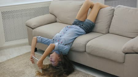 lefekvés : Funny teen girl relaxing on sofa upside down using laptop and surfing the internet