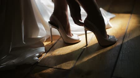 high heeled sandals : Bride arranges her wedding shoes and covers them with white wedding dress. Close up view.