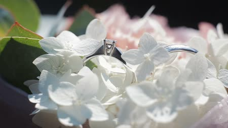 новобрачный : Wedding rings on a bouquet of white flowers. Rotating composition of Wedding rings and bouquet of white and pink flowers with green leaves. Close up.