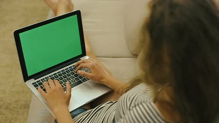 plavé vlasy : Close-up of a Teenage girl on a sofa typing on a laptop, searching the web. Teen girl with laptop is smiling to the camera. Green screen. Dostupné videozáznamy