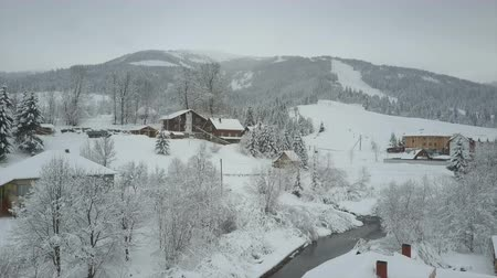karpaty : Rising up above a village in Carpathian mountains. Birds eye view of snow-covered houses in mountains. Rural landscape in winter. Carpathian village in the snow from a height.