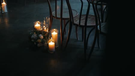 hortensia : Burning candles with beautiful bouquet of different flowers near a chair. Stock Footage