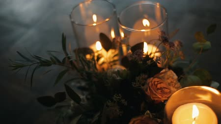 hortensia : Burning candles with beautiful bouquet of different flowers on a parquet floor. Candles burn in glasses.