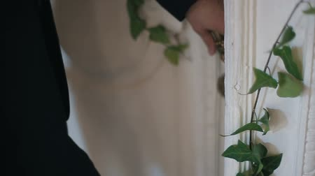 защелка : Man in black suit opens white old vintage door with brass handle decorated with green ivy. Man pushes the door and enters an old fashioned bright room decorated with burning candles.