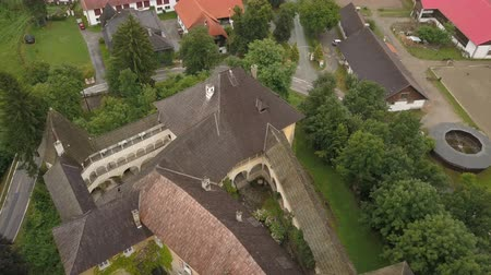 известное место : Aerial view of Medieval Castle Halleg in Klagenfurt, Austria, Karyntia. Flight over beautiful castle surrounded by Mountains and forests. Walls covered with ivy. Стоковые видеозаписи