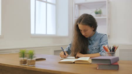 essay : Young girl with laptop computer is doing homework. College education. Female student is studying at home.