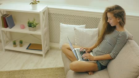 netbook : Happy teen girl on a couch uses laptop.