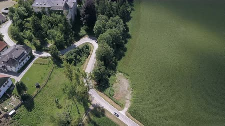 Aerial footage of a black open car moving along the road between green fields.
