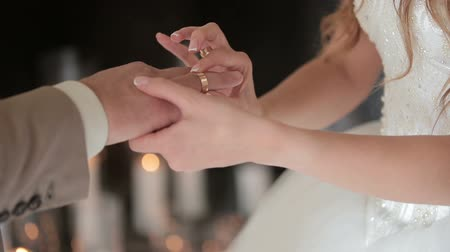 Bride wears ring on grooms finger. The bride and groom exchange wedding rings.