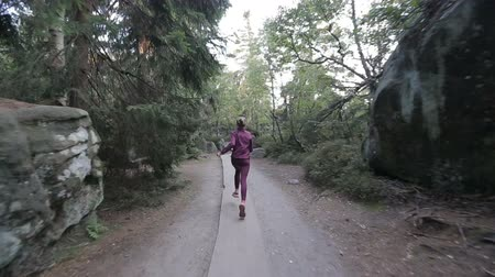 Young woman runs through a tourist pass among rocks and stones. Tracking shot with stabilized camera