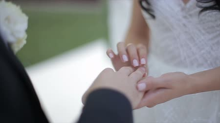 engaged : Bride wears ring on grooms finger. The bride and groom exchange wedding rings.