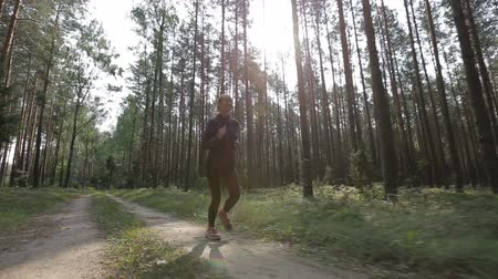 stabilizátor : Happy young woman is jogging in a forest among trees. Tracking shot with stabilized camera Stock mozgókép