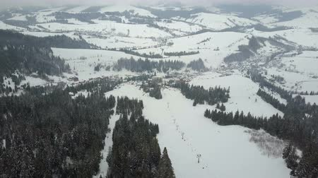 tirol : Flight over a ski resort in Carpathian mountains. Aerial view of snow-covered houses in mountains.