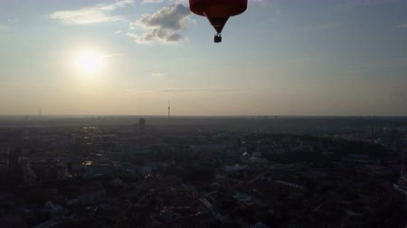 montgolfière : Hot air balloon floating over city at dawn, sun rising on horizon, aspirations