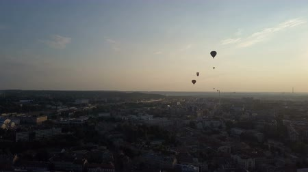 litvanya : Aerial view of hot air balloons over Vilnius city, Lithuania. Hot air balloons floating over city at dawn. Stok Video
