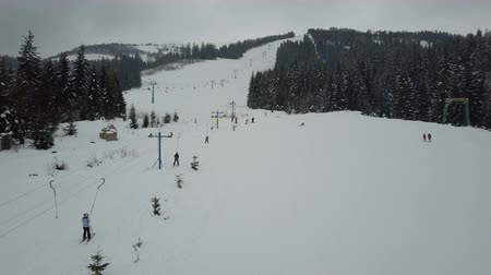 Flight over a ski lift in Carpathian mountains. Aerial view of ski resort.