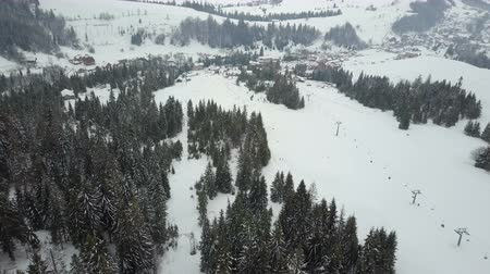 chata : Flight over a ski resort in Carpathian mountains. Aerial view of people descending on skis.