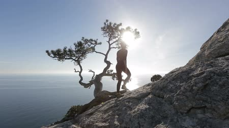 tourist silhouette : Young woman climbing and reaching the top of a mountain. Lady on the summit in beautiful scenery facing the seashore.