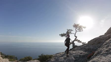 альпинист : Young woman walking and running on a mountain. Lady on the summit in beautiful scenery facing the seashore.