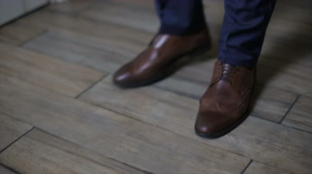 footgear : Man wearing trousers and brown leather shoes is walking indoors. Tracking shot of mans leather shoes, close-up view.