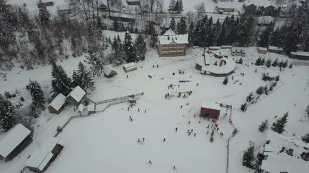 karpaty : Carpathian ski resort from a height. Flight over ski lifts. Birds eye view of people descending on skis and snowboards.