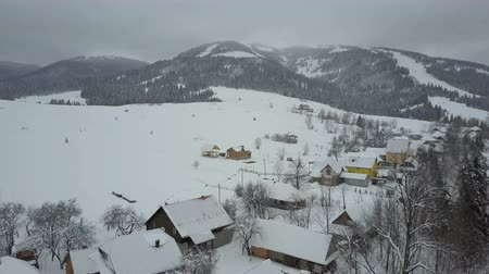 berghut : Flight over a village in Carpathian mountains. Birds eye view of snow-covered houses in mountains. Rural landscape in winter. Carpathian village in the snow from a height.