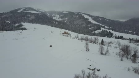 baita : Flight over a village in Carpathian mountains. Birds eye view of snow-covered houses in mountains. Rural landscape in winter. Carpathian village in the snow from a height.