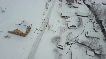 baita : Fast flight over a car moving on winter road in Carpathian village. Birds eye view of snow-covered houses. Rural landscape in winter. Filmati Stock