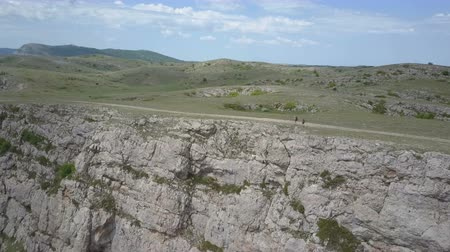 krím : Two girls walking in mountains on the edge of an impressive cliff in Crimea