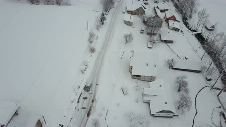 faház : Fast flight over a car moving on winter road in Carpathian village. Birds eye view of snow-covered houses. Rural landscape in winter. Stock mozgókép