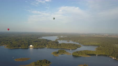 umutlu : Flight over beautiful Trakai castle at sunset in summer season. Aerial view of beautiful castle on the lakes in Lithuania. Hot air balloons floating over the castle. Stok Video