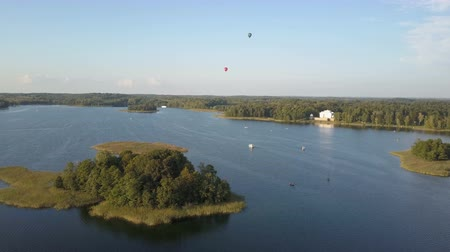 litvánia : Hot air balloons flying over beautiful lakes and islands in Lithuania near the Trakai castle in summer. Aerial view. Stock mozgókép