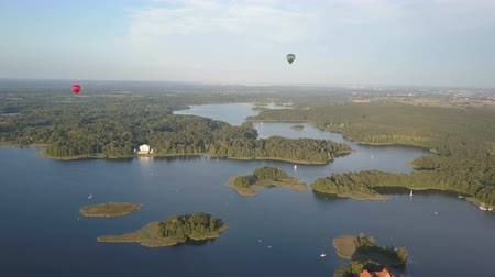 umutlu : Hot air balloons flying over beautiful lakes and islands in Lithuania near the Trakai castle in summer. Aerial view. Stok Video