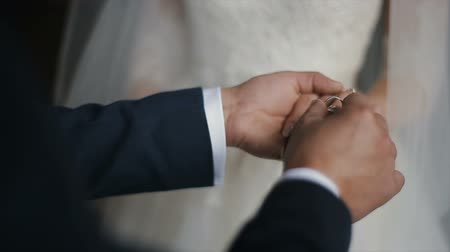 engaged : The groom puts the wedding ring on finger of the bride. marriage hands with rings. The bride and groom exchange wedding rings. Stock Footage