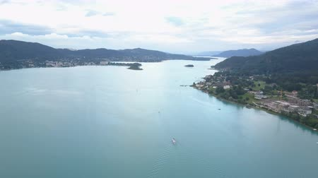 Aerial view of a big lake in mountains. Boat moves on the lake. Klagenfurt Carinthia Austria.