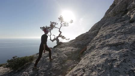 альпинист : Young woman walking high in mountains above a sea. Lady on the summit in beautiful scenery observing Black sea from a hight in Crimea.