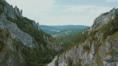 rali : Aerial view of a mountain road in a beautiful deep gorge. Cars move on a mountain road.