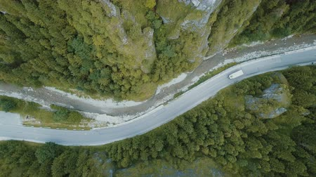 birdseye : Top panoramic aerial view of a truck moving on a mountain road in a beautiful deep gorge.