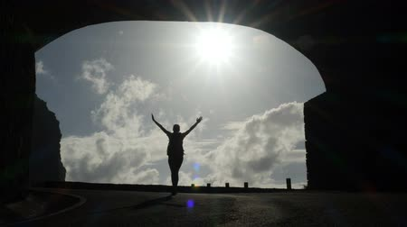 galo : Camera follows a woman silhouette walking out from tunnel towards the sunlight. Burst of bright light. Raising arms in the air. Stock Footage