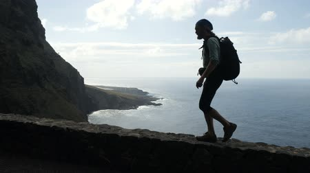 teneryfa : Male hiker with backpach is walking on the edge of a road in canary islands high above the ocean.