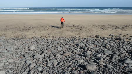 хорошее настроение : Young man rides a bicycle on big stones towards a sand beach on Canary Islands. Lanzarote, Atlantic ocean